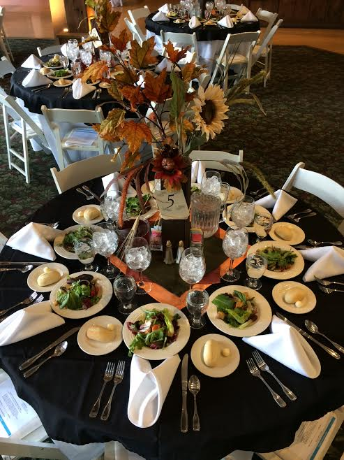 Table setting showing pre-set salads and dinner rolls